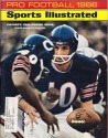 Sammy Baugh hands off to Gayle Sayers - Pro Football Issue